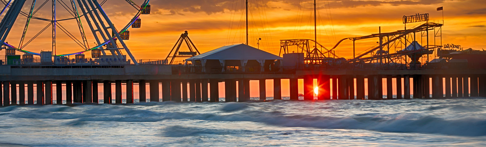 Steel Pier at sunrise with sun peaking through pier with ocean waves crashing.